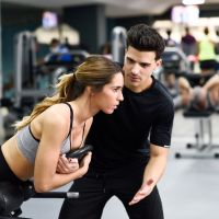 Personal trainer helping young woman lift weights while working out in a gym